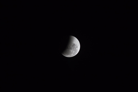 Moon view in the end (penumbra) of period of rare lunar eclipse phenomena which named Super Blue Blood Moon. The moon surface was half covered by the earth shadow.