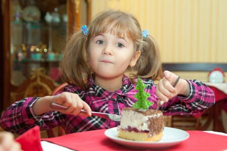 little girl starts eating a cake decorated with sugar fir