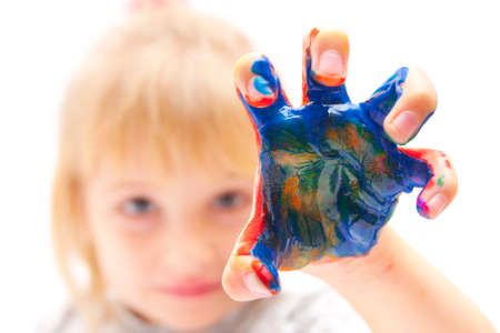 little girl making a grab move with hand in paint Stock Photo