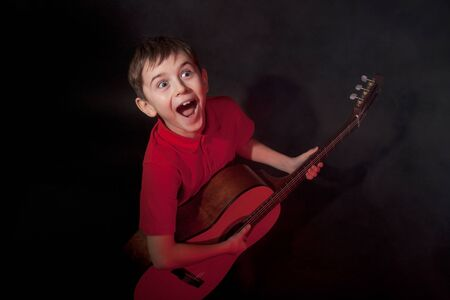 Emotionally singing boy with acoustic guitar on black background