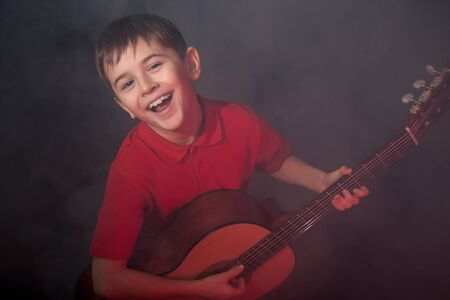 Happily singing boy with acoustic guitar in fog on stage
