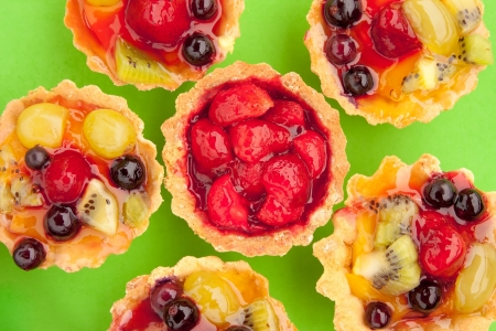 Close-up of tarts with strawberry and other different fruits and berries in jelly