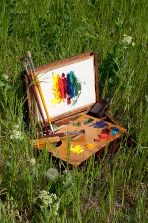 Compact vintage painter s case on grass with palette, artistic tools and abstract painting Stock Photo