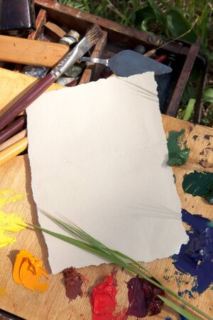 Textured paper on palette with painter instruments on the grass