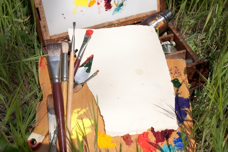 palette knife: Textured paper on palette lying on painter case on the grass