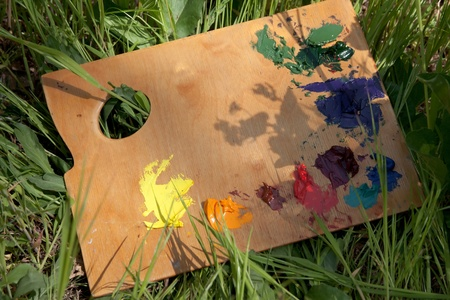 Palette with oil paint lying on the grass