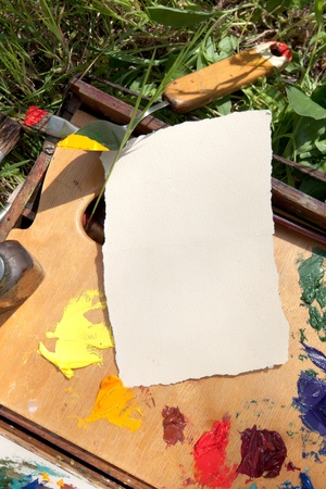 Textured paper on palette lying on painter case on the grass photo