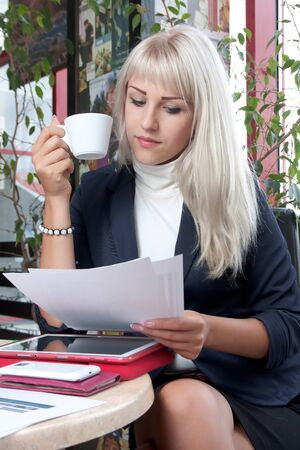 young woman watching business papers and drinking coffee in cafe