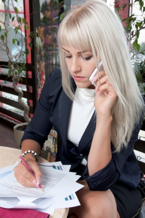 business woman talking to cell phone and working with business papers
