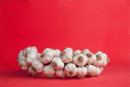 garlic bunch on a bright red