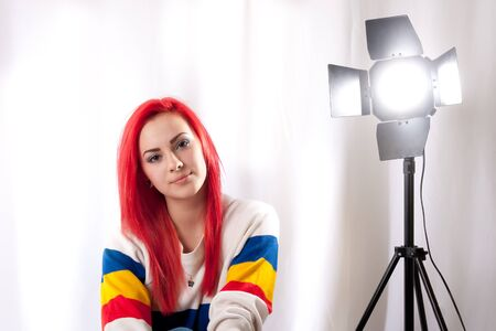 girl with bright red hair with a studio flash on a stand Stock Photo