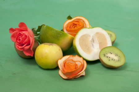 Still-life with roses and fruits on a green  Stock Photo