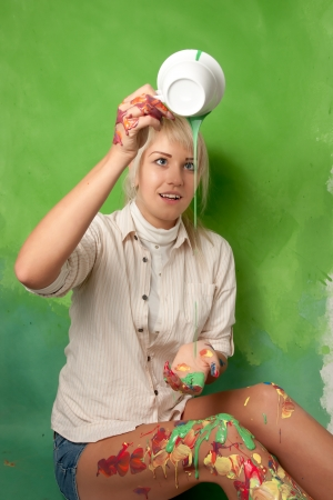 Attractive young girl pouring a green paint on herself from a cup