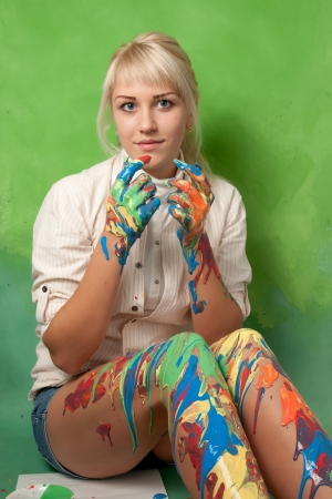 Attractive young painter covered with paint on a bright green