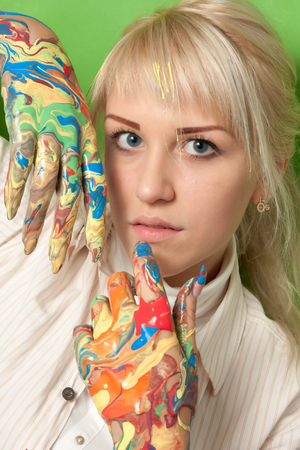 Portrait of a young girl with hands in fresh paint