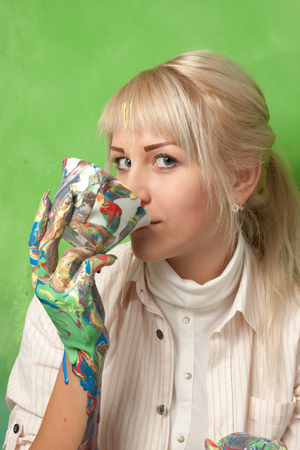 young attractive girl with a colored hands drinking from a smudged cup Stock Photo - 22844703
