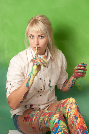Attractive woman with hands and legs covered with paint makes a hush and secret gesture Stock Photo