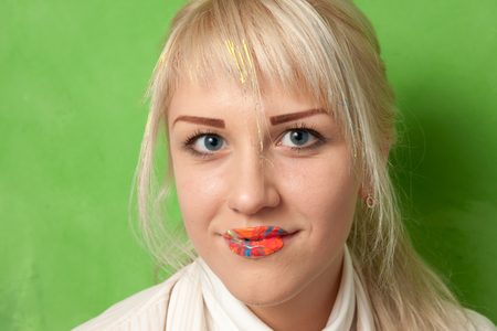 Portrait of an attractive smiling girl with lips in bright paints