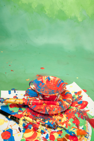 Card with a tea cup and a saucer full of bright paints with painting tools