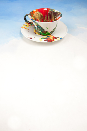 Card with white cup and a saucer smudged with paint on a white and blue background