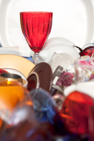 Red glass wine cup and a mass of bright kitchen utensils