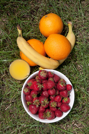Strawberries, oranges, bananas and a glass of orange juice on a lawn