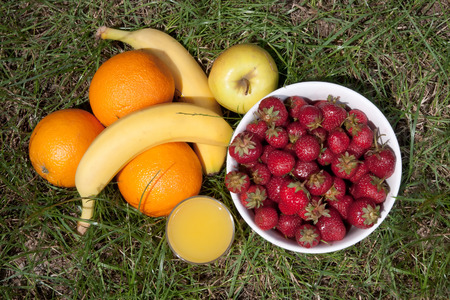 Strawberries, oranges, bananas, apple and a glass of orange juice on a lawn