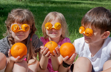 Children wearing crazy peel glasses and holding oranges Stock Photo