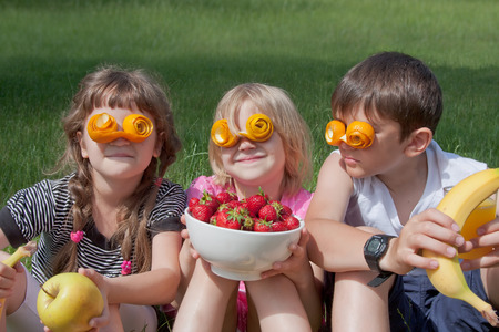 Children wearing crazy orange peel glasses and holding different fruits