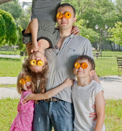 Family wearing a crazy orange peel glasses celebrating day of fathers in a park