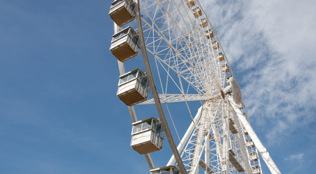 View of Observation Wheel Against the Blue Sky With Clouds Stock Photo