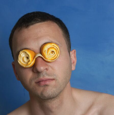 Portrait of a Man With Crazy Orange Peel Eyeglasses on Blue Background Stock Photo