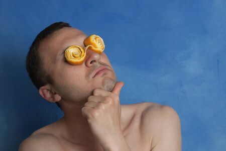 Portrait of a Thinking Man With Crazy Orange Peel Spectacles on Blue Background Stock Photo