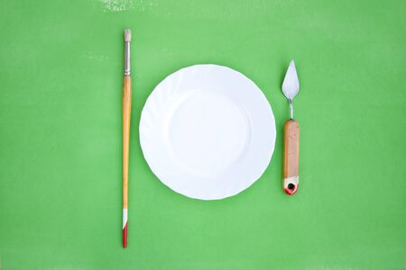 White plate with paintbrush and a palette knife on bright green background