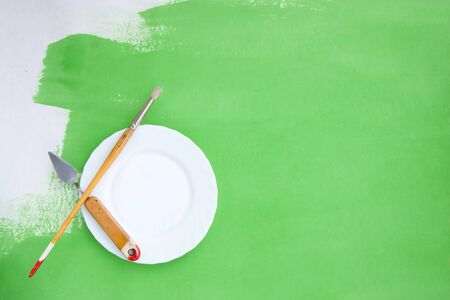 Artistic bright green and white background with a brush, palette knife and a plate Stock Photo