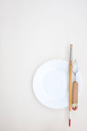 White background with vintage paintbrush and a palette knife on a white plate Stock Photo