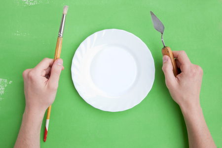 Top view of a plate and hands of a person with artistic instruments on a bright green Stock Photo