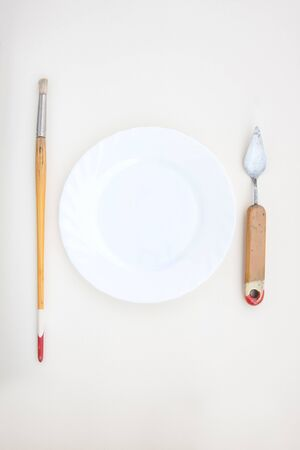 Vintage paintbrush and a palette knife with a white plate on a white background