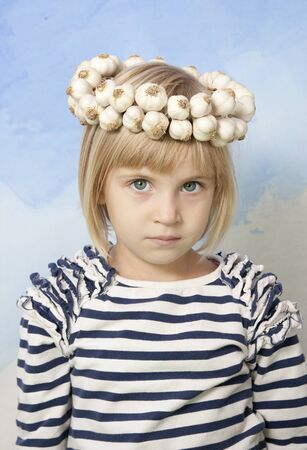 Little girl with Ukrainian traditional wattled garlic wreath on her head
