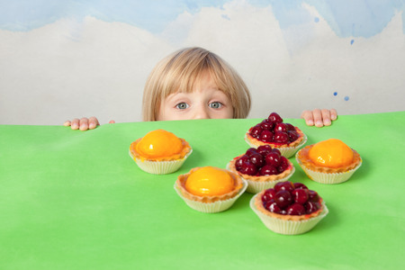 Little pretty girl emerging from behind a table with cherry and peach jelly tarts Stock Photo
