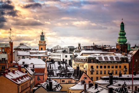 Winter sunset over snow covered old buildings roofs, Stockholm, Sweden.