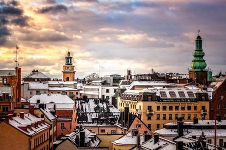 sweden: Winter sunset over snow covered old buildings roofs, Stockholm, Sweden.