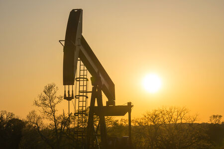 The Sun sets behind a Texas oil well.