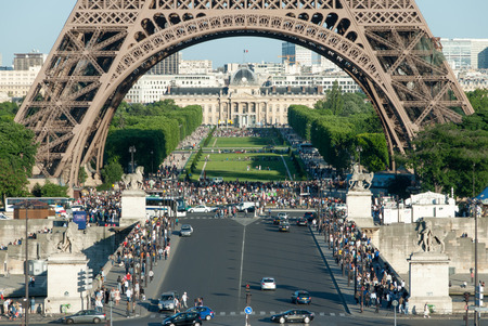 d'eiffel: Crowds beneath the Eiffel Tower arches with a view of Champs de Mars and statues on the Pont d