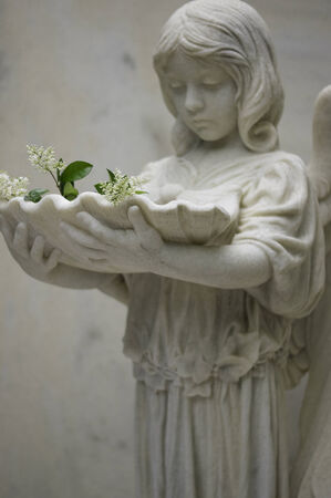 solemnity: Angel Holding Font with Flowers V Stock Photo