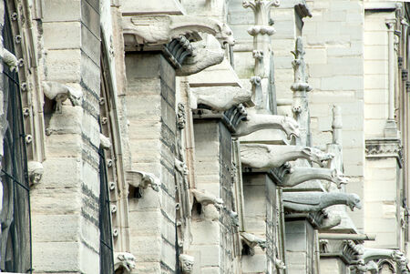 protrude: Gargoyles Protrude from a Wall of Notre Dame Cathedral. Stock Photo