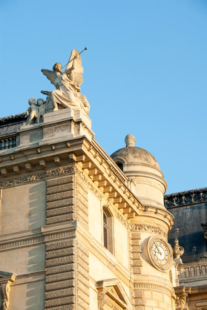 cherubs: Angel with trumpet and cherubs, and clock tower at the Louvre. Stock Photo