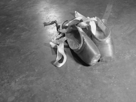 A pair of old, worn-out pointe shoes. photo