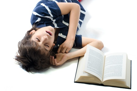Young boy falling asleep while studying on school book, isolated on white photo