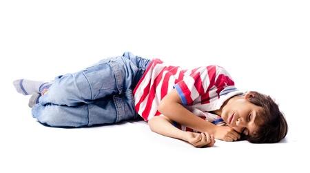Fáradt, kimerült gyermek alszik a földön, elszigetelt fehér háttér